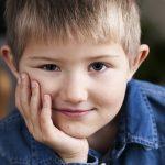 En leende pojke som sitter med hakan i handen.