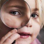 En flicka tittar genom ett förstoringsglas.